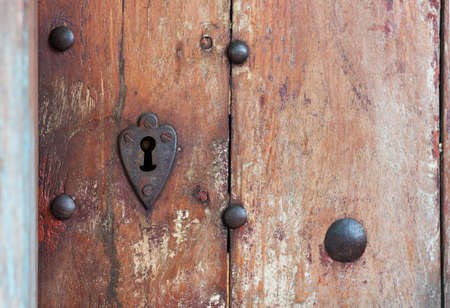 heart shaped: Heart shaped keyhole surround in old wooden door.