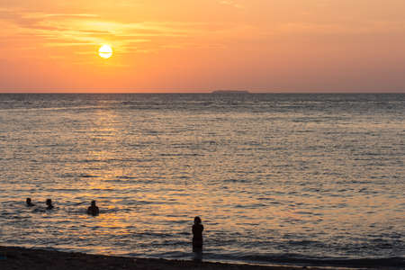Silhouetted beach goers in a calm tropical sea during a pastel sunset with an island on the horizon.