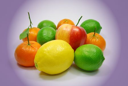 Limes, lemon, aple and tangerines .Fruits on white background close up, Center isolated from colourful soft blurry background.