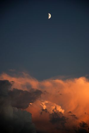 Half moon over Dramatic clouds at sunset Stock Photo