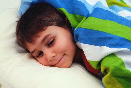 Sleepy Cute boy in his bed. Six seven year old boy.