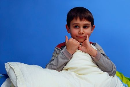 Cute boy in his bed. Six seven year old boy.