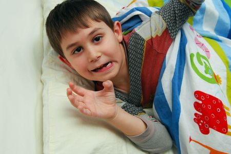 Cute playful boy in his bed. Six seven year old boy.
