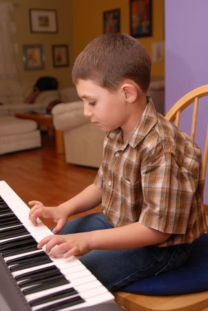 preadolescent: A Young boy playing piano or keyboard,6-7 year old. Stock Photo