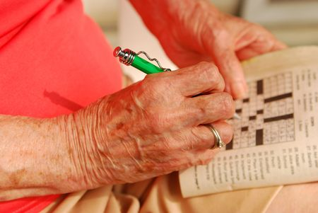 Hands of senior woman solving a  crossword puzle. Stock Photo