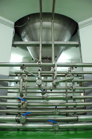 distillate: Pipes and fermenting tank in modern Breery