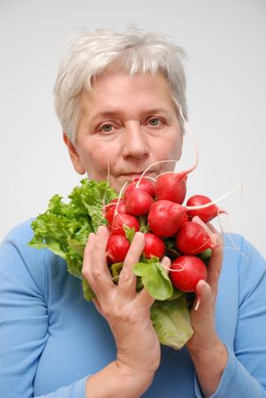 A mature woman holdind a bunch of Radishes. Image isolated on white Stock Photo