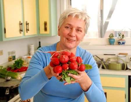A mature woman holdind a bunch of Radishes in Her kitchen, Stock Photo