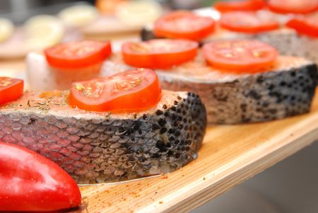 A raw Salmon with tomatoes , ready oo grill. Close up