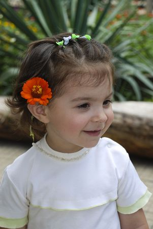 Adorable little girl with an orange flower in her  hair