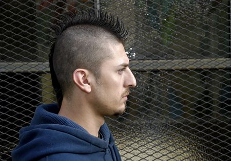 Profile portrait of Hispanic  man with spiked Mohawk against a grudge background.