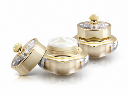 Two golden crown cosmetic jar on white background