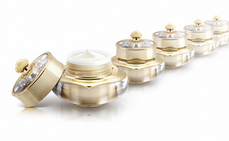 Several golden crown cosmetic jar on white background