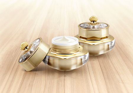 Golden crown cosmetic jar on wood background