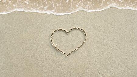 Symbol written in the sand on the beach Standard-Bild
