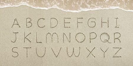 Alphabet letters handwritten in the sand on the beach Standard-Bild - 147298365