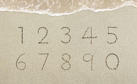 Alphabet letters handwritten in the sand on the beach Standard-Bild