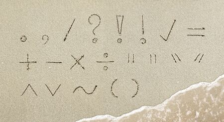 Punctuation mark handwritten in the sand on the beach