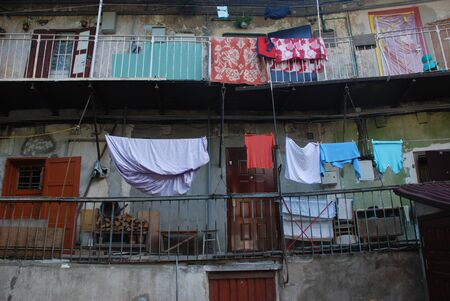 Wet laundry is hanging on the old town balcony and drying. 版權商用圖片