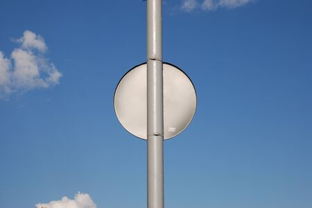 Back Side of rounded street sign which is hanging on the pillar in field sky field.