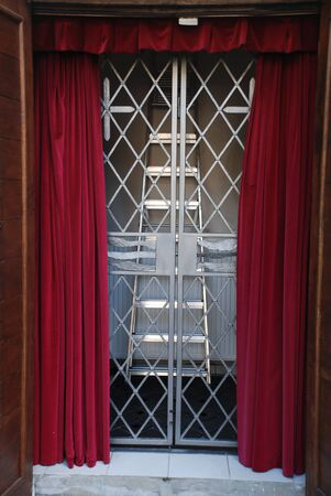 Red theater curtains with wavy  and the curtains pulled away. Also there are stairs and  grating. 版權商用圖片