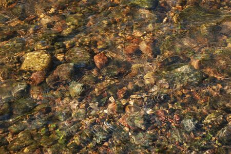 Soft wavy water river with flowing  water above the stones. Transparent water with sand and stones.