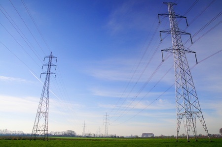 Elictric power grid with pylons in landscape Stock Photo