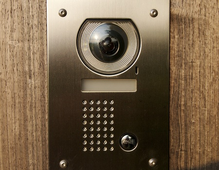 Intercom with camera on wooden front door Stock Photo