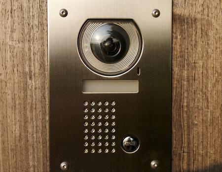 Intercom with camera on wooden front door photo