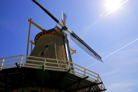 Old windmill in the blue sky with the sun