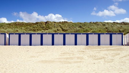 Wooden cabins on a sunny blue sky beach in blue and white