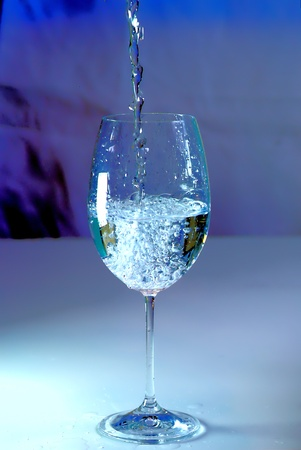 Water poring in a glass with blue shade