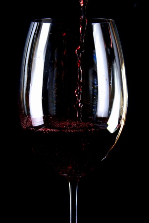 Red wine pouring in a glass isolated on black