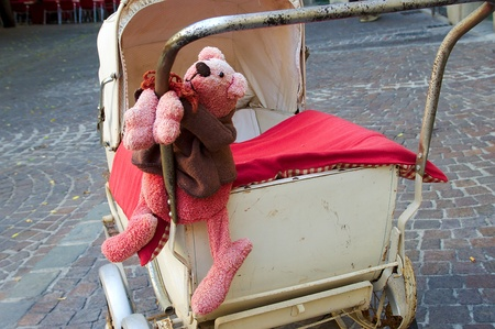Pink teddy bear hanging on antique baby carriage Stock Photo