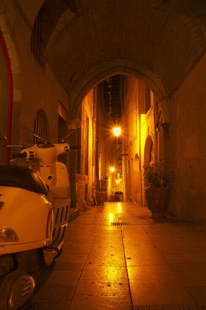 Little alley at night in old centre of Montpellier, France  with white scooter Stock Photo
