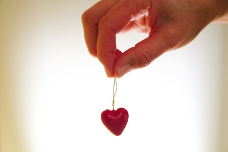 Woman hand holding red valentine heart on golden string Stock Photo