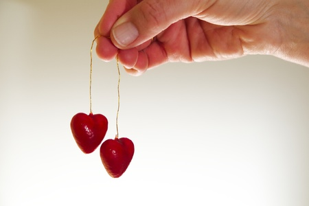 Woman hand holding two red valentine hearts on golden strings Stock Photo - 11928816
