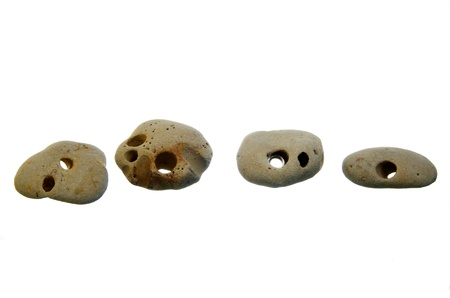 Four perforated stones isolated on white