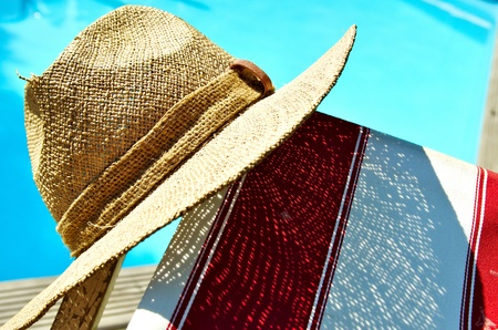 Straw hat, deck chair and swimming pool photo