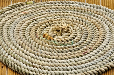 A rope in circles on te wooden deck of a boat Stockfoto