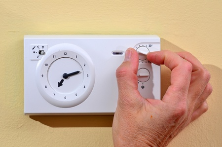 save heating costs: Seniors adjusting thermostat to save on heating costs Stock Photo