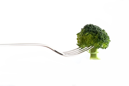 Broccoli on a silver fork on white background