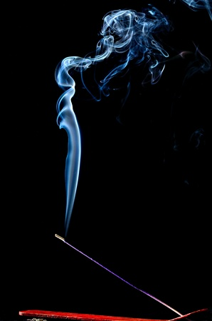Burning lavender incense stick and smoke on black photo