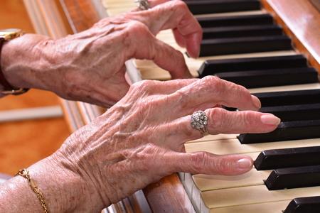piano: Mujer de edad de cerca de las manos tocando el piano