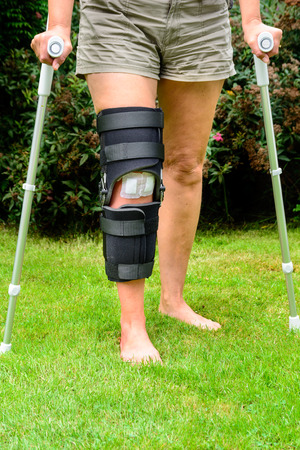 Woman with knee in brace after injury and surgery Stock Photo - 30575754