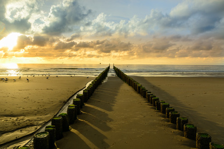 breakwaters: Breakwaters on the beach at sunset in Domburg, Zeeland,  Holland Stock Photo