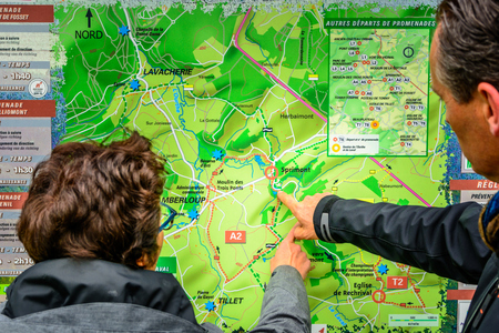the ardennes: Man and woman looking on a map to start a hike in Belgian Ardennes Editorial