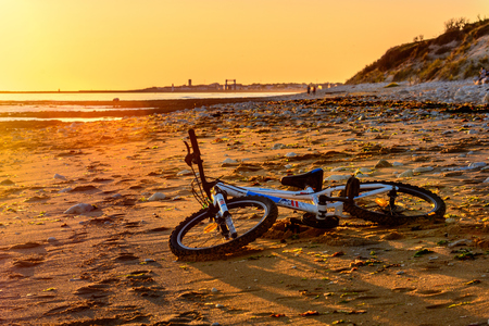 bmx bike: Bmx bike laying on the beach in France at sunset Stock Photo