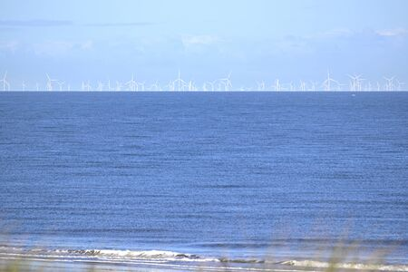 Offshore wind farm in the north sea as seen from the beach in Cadzand, The Netherlands Stock Photo - 137271676