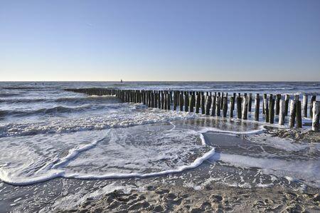 Breakwaters on a winter beach in Vlissingen Holland Stock Photo - 142780963